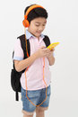Happy Asian boy ware headphone and playing the cell phone . Royalty Free Stock Photo