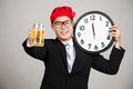 Happy asian businessman with beer and clock at midnight on gray background Stock Image