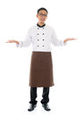 Happy asian chef welcoming pose full body male hands showing blank space welcome guest concept standing isolated white background Stock Image