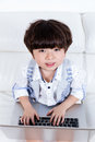 Happy Asian Chinese little boy sitting on couch with laptop Royalty Free Stock Photo