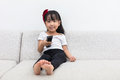 Happy Asian Chinese little girl holding a TV remote control Royalty Free Stock Photo