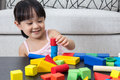 Happy Asian Chinese little girl playing building blocks at home