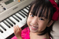 Happy Asian Chinese little girl playing electric piano keyboard Royalty Free Stock Photo