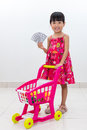 Happy Asian Chinese little girl pushing toy trolley holding cash Royalty Free Stock Photo