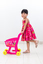 Happy Asian Chinese little girl pushing toy trolley Royalty Free Stock Photo