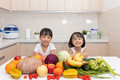 Happy Asian Chinese little sisters with fruit and vegetable Royalty Free Stock Photo