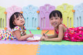 Happy Asian Chinese little sisters laying on the floor coloring