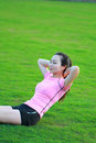 Happy Asian Chinese woman do sit-up on grass Royalty Free Stock Photo