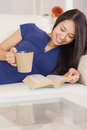 Happy asian girl lying on the sofa reading a novel and drinking hot beverage in living room at home Royalty Free Stock Photography
