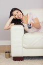 Happy asian girl lying on the sofa watching tv at home in sitting room Stock Photo