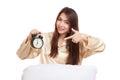 Happy Asian girl  wake up point to alarm clock Royalty Free Stock Photo