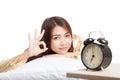 Happy Asian girl  wake up show OK with alarm clock Royalty Free Stock Photo