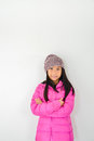 Happy Asian girl wearing pink down jacket sitting on gray Royalty Free Stock Photo