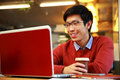 Happy asian man in glasses working on laptop and holding cup of coffee Stock Image