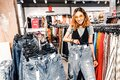 Asian woman looking for jeans in clothes store. Shopping and lifestyle concept Royalty Free Stock Photo