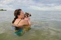 Happy Asian women girl hug play immersed in beach sea water with cute dog puppy pug with kiss in weekend holiday Royalty Free Stock Photo