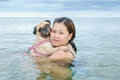 Happy Asian women girl hug play immersed in beach sea water with cute dog puppy pug Royalty Free Stock Photo