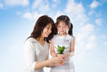 Happy asian young mother daughter taking care plant summer day blue sky as background Stock Photos