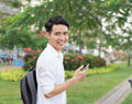 Happy Asian young student using mobile phone Royalty Free Stock Photo