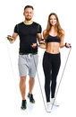 Happy athletic couple - man and woman with with ropes on the whi