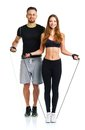 Happy athletic couple - man and woman with ropes on the white