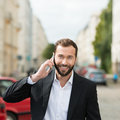 Happy attractive businessman on his mobile phone chatting as he walks along an urban street looking at the camera with a beaming Royalty Free Stock Photo