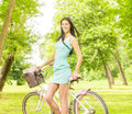 Happy attractive girl with bicycle in the park at beautiful spring day Royalty Free Stock Photography