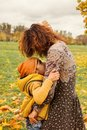 Happy Autumn Family. Cute Mother and Son Hugging in Fall Park Royalty Free Stock Photo