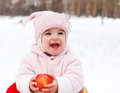 Happy baby with apple in winter park smiling Royalty Free Stock Photography