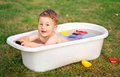 A happy baby bathed in the bath and playing with toys. Royalty Free Stock Photo