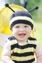 Happy baby in bee costume sitting on baby carriage age of months Stock Image