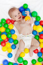 Happy baby boy with lots of colorful balls in diapers playing Stock Photo