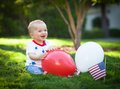 Happy baby boy playing with rend and white balloons Royalty Free Stock Photo