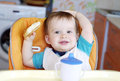 Happy baby boy with round cracknel age of year and cup of tea on kitchen Royalty Free Stock Photography