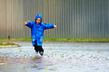 Happy baby boy running the street, rainy weather Stock Photography