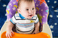 Happy baby boy is sitting at the childrens table with asterisks Royalty Free Stock Images