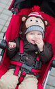 Happy baby boy sitting in a red stroller for walk Stock Photos