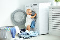 Happy baby boy to wash clothes and laughs in laundry Royalty Free Stock Photo