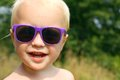 Happy baby boy wearing sunglasses close up portrait of a cute is purple and smiling as he looks at the camera outside on a sunny Stock Photography