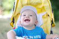 Happy baby boy on yellow baby carriage in summer age of months Stock Image