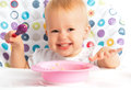Happy baby child eats itself with a spoon cheerful Royalty Free Stock Images