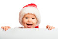 Happy baby in a christmas hat and a blank billboard isolated on white background Stock Photo