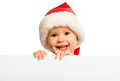 Happy baby in a Christmas hat and a blank billboard isolated on
