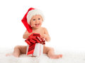 Happy baby in a christmas hat with a gift isolated on white background Stock Images