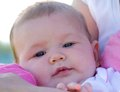 Happy baby a close up portrait of a young infant safe in her mothers arms Royalty Free Stock Photo
