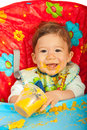 Happy baby eating puree sitting in chair and vegetables Stock Photography