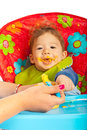Happy baby eating puree vegetables and sitting in chair Stock Image