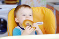 Happy baby eating round cracknel boy age of year on kitchen Stock Image