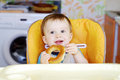 Happy baby eating round cracknel on kitchen boy age of year Royalty Free Stock Images