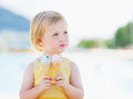 Happy baby eating two ice cream horns and looking on copy space Royalty Free Stock Photo